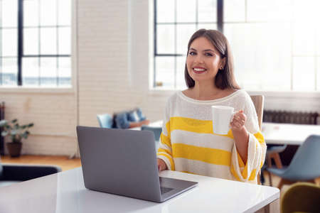 A beautiful, smiling woman with a cup of coffee works on her laptop in a bright office room
