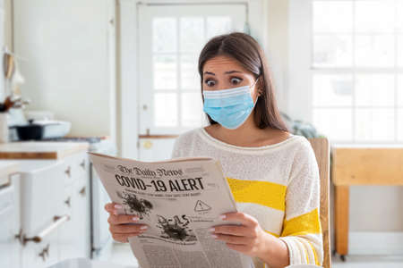 A scared young woman wearing a face mask sits on the kitchen table and reads the morning newspaper with bad news about Covid-19 pandemic