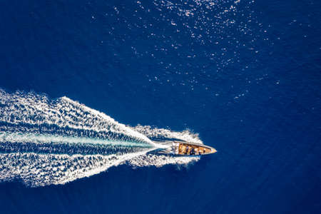 Aerial top down view of a motorboat traveling over blue sea 스톡 콘텐츠