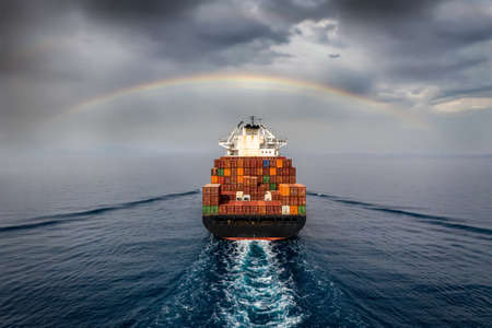 Aerial view of a container cargo ship sailing into bad weather with a rainbow in the cloudy sky