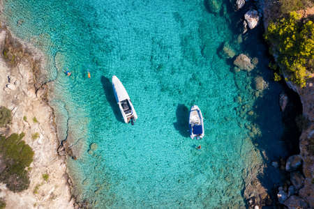 Aerial view of moored rib boats with snorkelers and swimmers at the turquoise colored coast of the Aegean Sea in Greece
