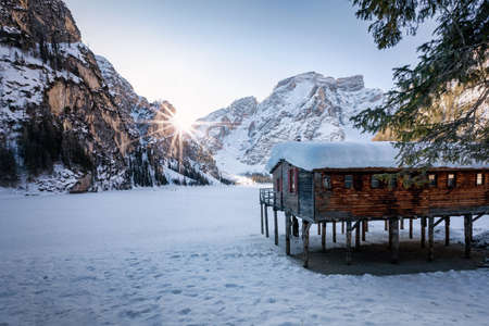 Sunrise behind the Dolomites Mountains at Lago di Braies with snow during winter time, Italy