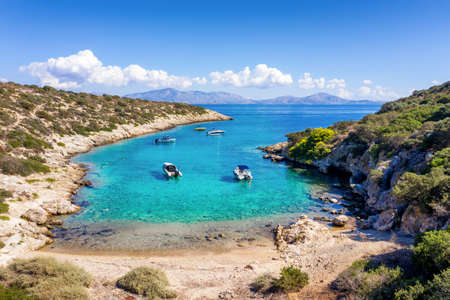 A small beach on the little island of Fleves, close to Athens, with turquoise sea and people enjoying the sun, Greece