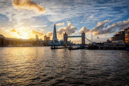 View to the Tower Bridge and modern skyline of London, United Kingdom, during a golden autumn sunset with reflections on the Thames river 스톡 콘텐츠