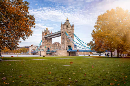 Beautiful view to the Tower Bridge of London, United Kingdom, with golden sunshine and colorful leafs on the trees during autumn time 스톡 콘텐츠