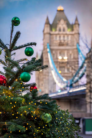 Defocused view the Tower Bridge in London, United Kingdom, with a decorated christmas tree in front