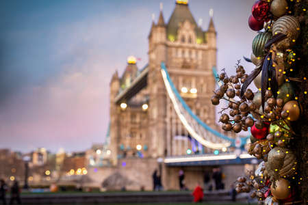 Defocused, conceptual view to the illuminated Tower Bridge in London, United Kingdom, with christmas decorations in front for the festive season