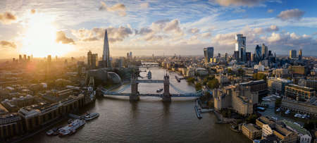 Elevated, panoramic view of the skyline of London, United Kingdom, with Tower bridge, the City and modern skyscrapers along the Thames river during sunset time
