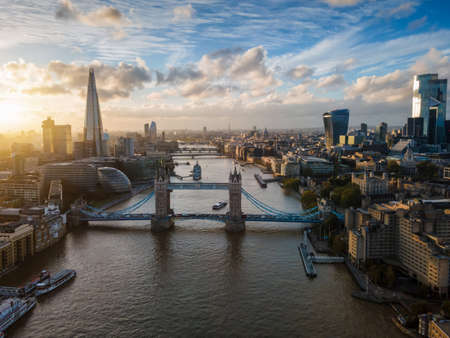 Wide panoramic view to the modern skyline of London, United Kingdom, along the Thames river during sunset time