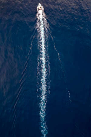 Aerial view of a boat sailing over blue water and leaving a trail of white bubbles