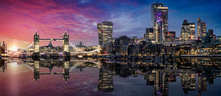 The lit urban skyline with City of London and Tower Bridge just after sunset time with reflections in the river Thames, United Kingdom 스톡 콘텐츠