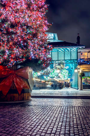 A illuminated Christmas tree for the festive winter season in the Covent Garden district, London, United Kingdom 스톡 콘텐츠
