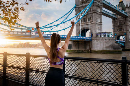 A young woman in sports clothing stands with outstretched arms in front of the skyline of London, UK, after a sunrise workout session
