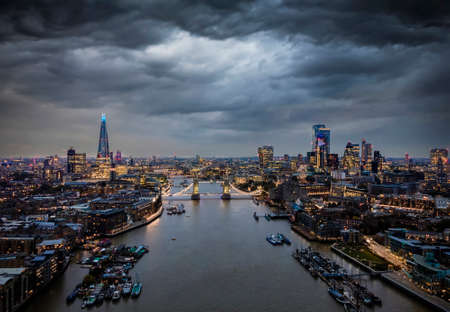 Elevated, moody view to the illuminated skyline of London, United Kingdom, with a cloudy sky during dusk 스톡 콘텐츠