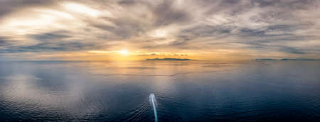 A boat traveling over idyllic, calm ocean towards an lonely island during sunset time with cloudscape in the sky 스톡 콘텐츠