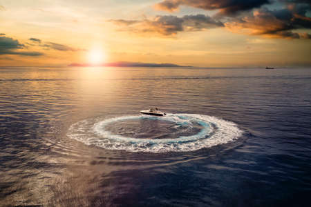 Aerial view of a motorboat forming a circle of waves and bubbles over calm sea during sunset time