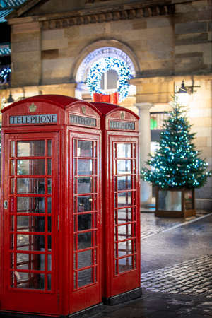 Red telephone booths in front of Christmas decorations lights in the Covent Garden district, London, United Kingdom