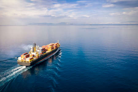Aerial view of a loaded cargo container ship traveling over calm ocean towards the next commercial port 스톡 콘텐츠
