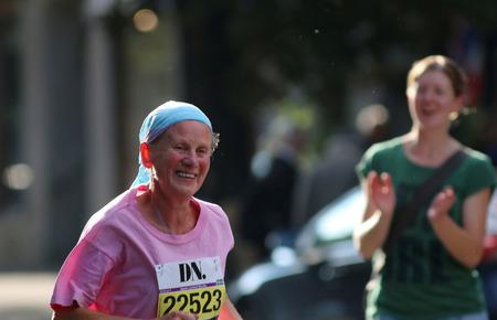 smilie: STOCKHOLM - SEPTEMBER 13, 2014: Happy old lady running in the Half marathon running event (21 km), Sept 13, 2014 in Stockholm, Sweden