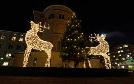 Two raindeer made of light posing in front of a christmas tree Stock Photo