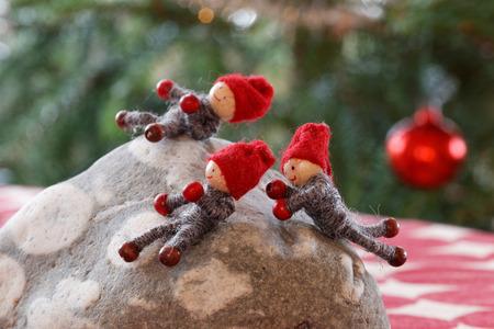 gnomos: Tres sonrientes gnomos de Navidad que juegan en una piedra