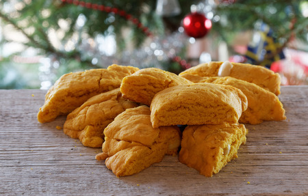 Yellow saffron biscuits in front of the christmas tree Standard-Bild