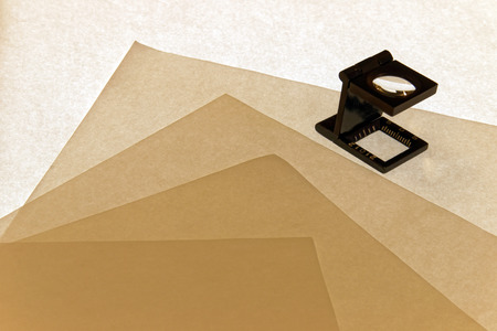 sceince: Loupe checking Formation of a stack of paper paper sheets