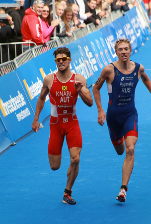 igor: STOCKHOLM - AUG 23, 2014: Alois Knabl (AUT) and Igor Andreyevich Polyanski (RUS) has a tough fight in the finnish of the Menss ITU World Triathlon series event August 23, 2014 in Stockholm, Sweden Editorial