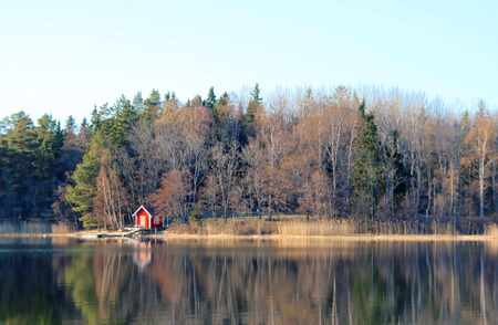 archipelago: Small red boat house reflecting in the sea  - Swedish archipelago