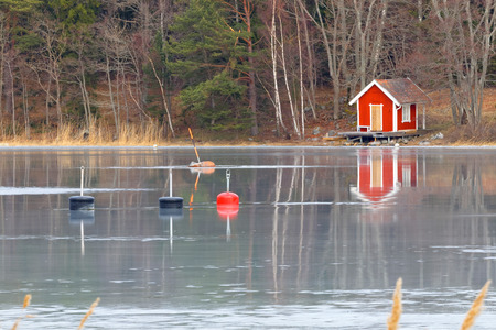 nautical structure: Red boat house reflectring in the ice  - Swedish archipelago