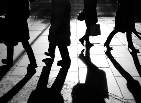 strangers: Dark silhouettes of the legs of four walking on the side walk in bright backlight
