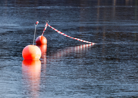 thin ice: Two orange buoys reflecting in the thin ice