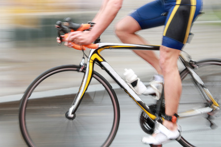 Side view of a very rapid professional male cyclist without torso dressed in a blue sport suit. Motion blur