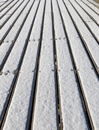 portrait orientation: Bridge made of plank partly covered with snow - portrait orientation