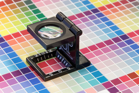 Close-up of a loupe on very colorful test print with color shades in cyan, blue, magenta, red, green, orange, and yellow