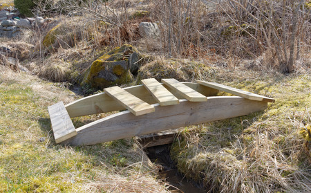 impregnated: Building a small wooden curved bridge over the trench built of impregnated wood