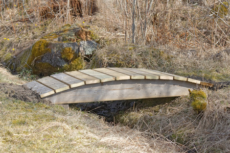 impregnated: Small wooden curved bridge over the trench built of impregnated wood