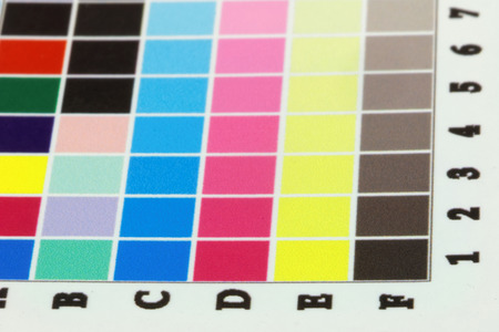 inkjet: Close-up of a a blurry inkjet cmyk test print with many color squares. Side view, short depth of focus