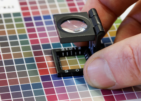 Close-up of a loupe on colorful, blurry inkjet test print with color dark shades in cyan, blue, magenta, red, green, orange, and yellow. Short DOF photo
