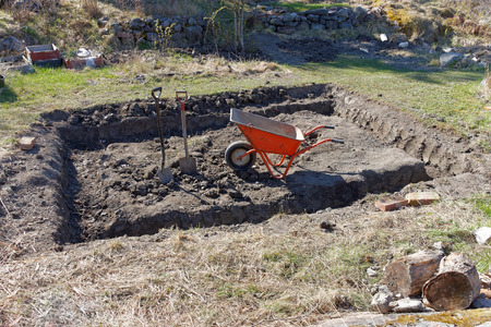 wheel house: Digging in the ground to preapare the foundation to a small house using a wheel barrow and spades Stock Photo
