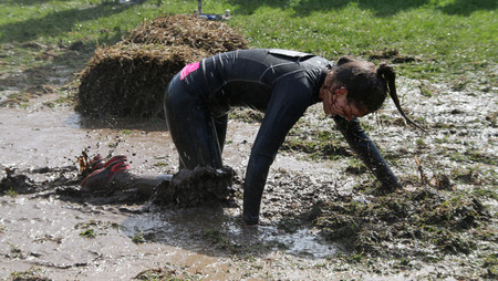 STOCKHOLM - MAY 09, 2015: Woman crawling on her knees through the mud during the last station of the public obstacle race event Tough Viking, May 09, 2015 in Stockholm, Sweden