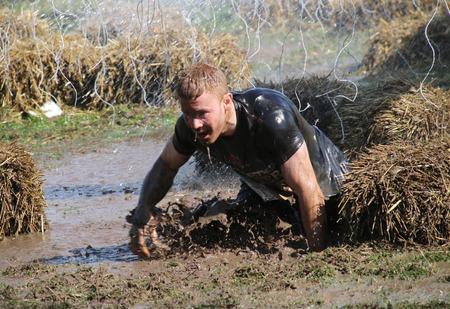 ストックホルム 2015 年 5 月 9 日: 集中、ハングを回避しようとしている泥に落ちる男スウェーデン ストックホルムで 2015 年 5 月 9 日公共の障害物レ