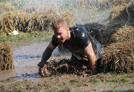 STOCKHOLM  MAY 09 2015: Focused man falling the mud trying to avoid the hanging electrified cabels during the last station of the public obstacle race event Tough Viking May 09 2015 in Stockholm Sweden