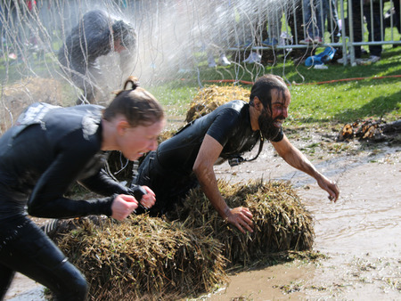 squirted: STOCKHOLM  MAY 09 2015: Woman and man fighting hard to get through the mud squirted with water trying to avoid the hanging electrified cabels during the last station of the public obstacle race event Tough Viking May 09 2015 in Stockholm Sweden Editorial
