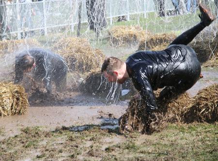 overturn: STOCKHOLM  MAY 09 2015: A man makes a spectacular overturn in the mud trying to avoid the hanging electrified cabels during the last station of the public obstacle race event Tough Viking May 09 2015 in Stockholm Sweden Editorial