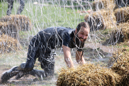 squirted: STOCKHOLM  MAY 09 2015: Man fighting the pain from the electified wires laying in the mud on his knees squirted with water during the last station of the public obstacle race event Tough Viking May 09 2015 in Stockholm Sweden