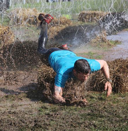 overturn: STOCCOLMA - 9 maggio 2015: Un uomo in t-shirt blu fa un rovesciamento spettacolare nel fango cercando di evitare l'impiccagione cabels elettrificati durante l'ultima stazione della manifestazione corsa a ostacoli pubblico Duro vichingo, 9 maggio 2015 a Stoccolma, Svezia