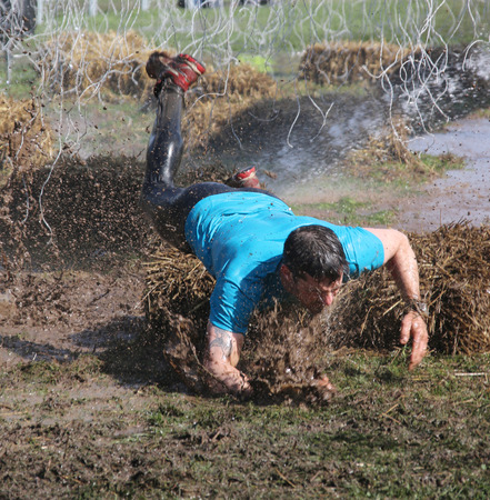 overturn: STOCKHOLM - MAY 09, 2015: A man in blue t-shirt makes a spectacular overturn in the mud trying to avoid the hanging electrified cabels during the last station of the public obstacle race event Tough Viking, May 09, 2015 in Stockholm, Sweden