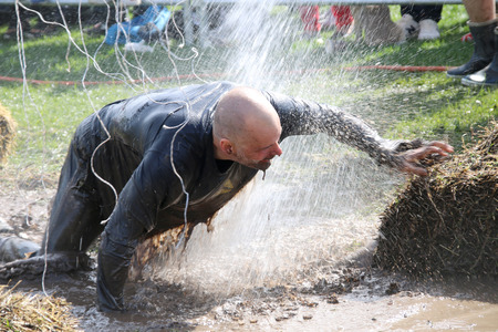 squirted: STOCKHOLM  MAY 09 2015: Man fighting to get through the mud on his knees squirted with water trying to avoid the electrified cabels during the last station of the public obstacle race event Tough Viking May 09 2015 in Stockholm Sweden
