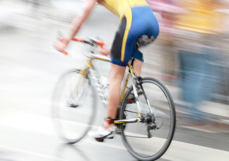 bicycling: A very fast bicycling man dressed in blue and yellow. The speed makes it unsharp Stock Photo